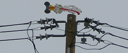 wires, a pole and a weathervane